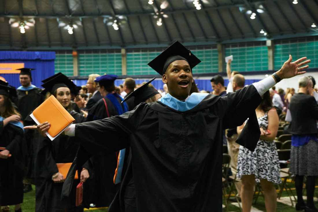 Student cheers in a cap and gown at graduation