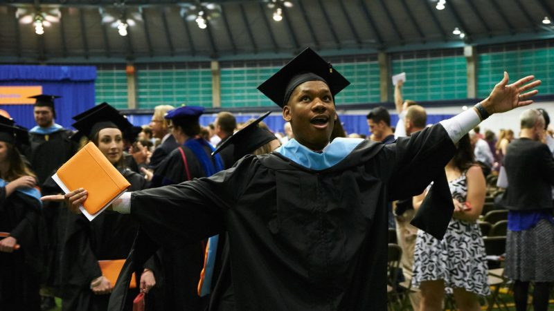 student in cap and gown cheering at graduation