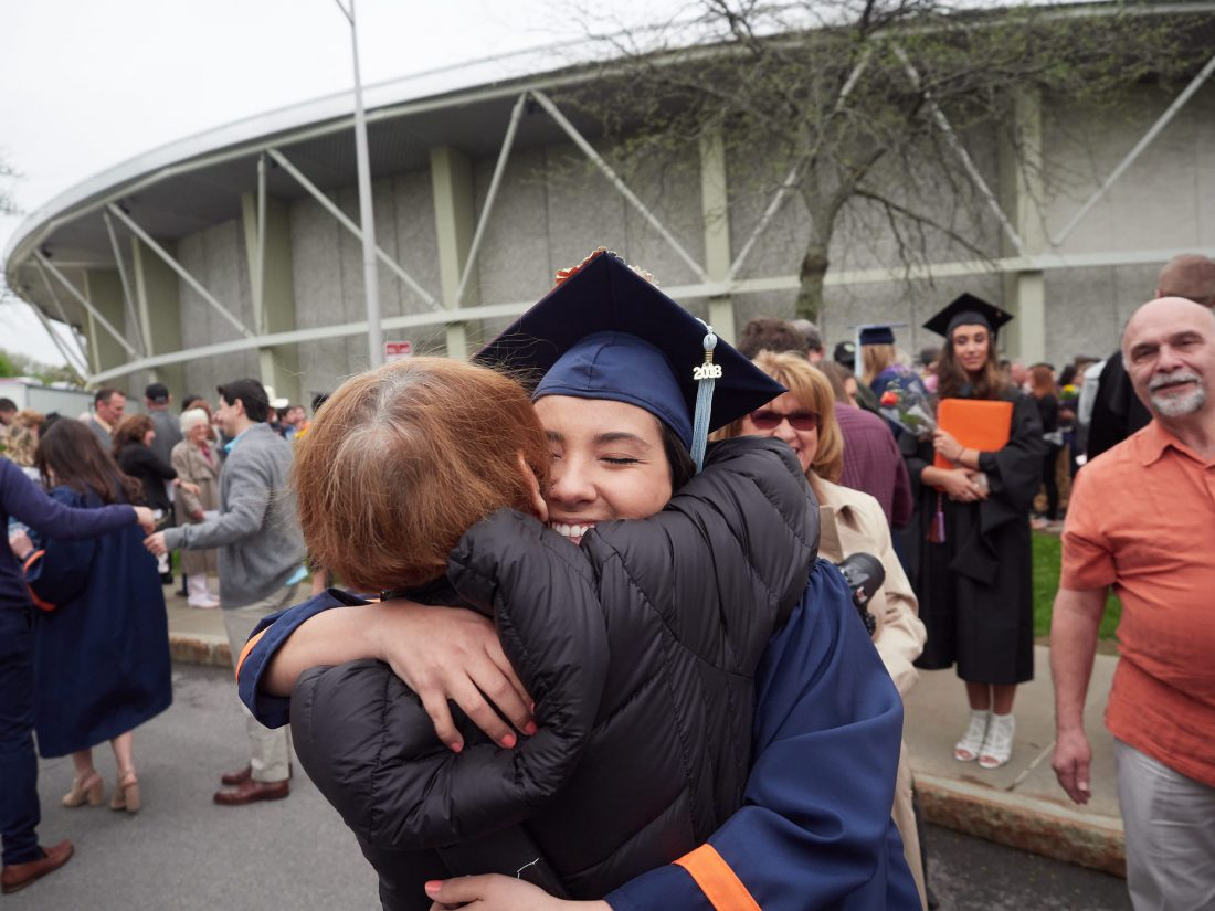 A graduate and family hug at graduation