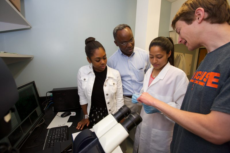 Scientists discuss data in front of a microscope.
