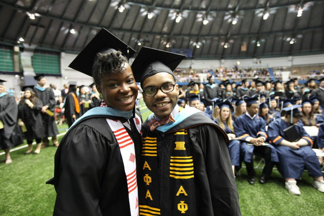 two students of color wearing master's caps and gowns at school of education graduation