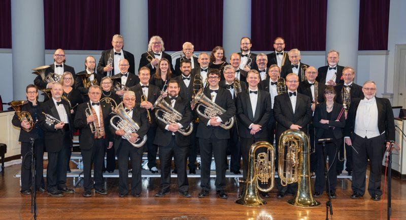 Musicians of the Syracuse University Brass Ensemble pose for a picture on the stage at Hendricks Chapel