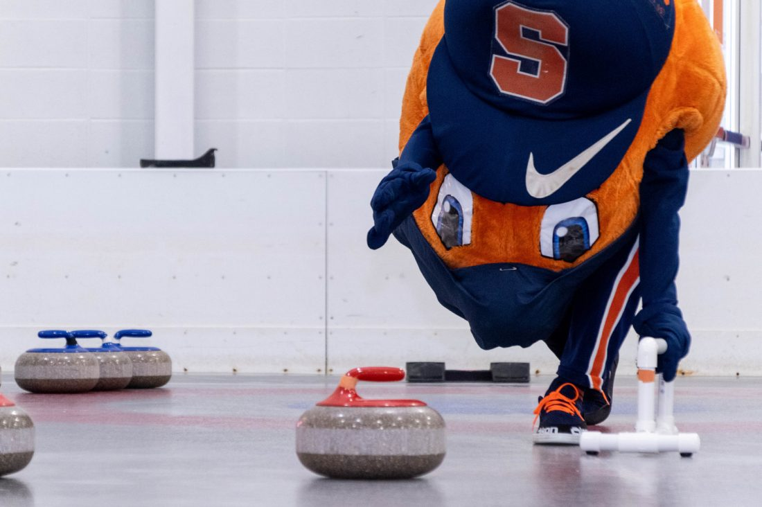 Otto the Orange practices their curling at Tennity Ice Skating Pavilion.