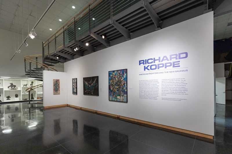 interior of a museum with a long white wall wiht text and artwork (paintings) installed