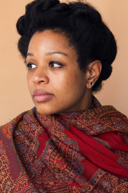 Black woman in profile with short dark hair and a bold red and brown scarf wrapped around her neck