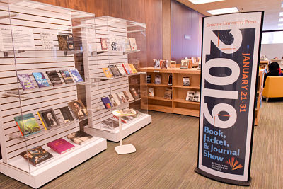 two white display cases with book jackets on shelves. Banner sign in front of display cases