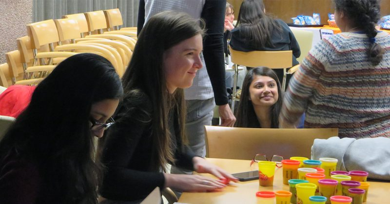 several students smiling, talking, playing with play-dough