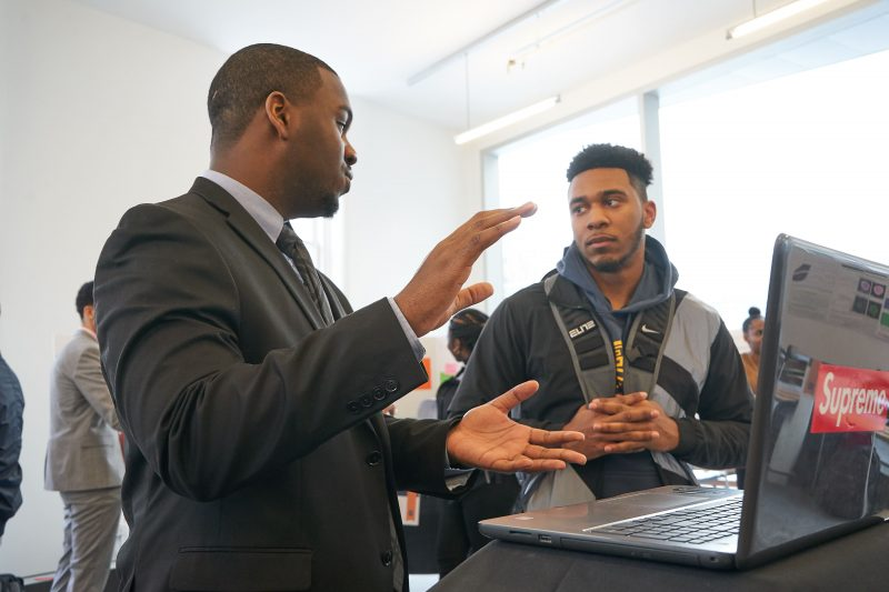 Student presents their research to a peer at the 2019 scholars of distinction showcase