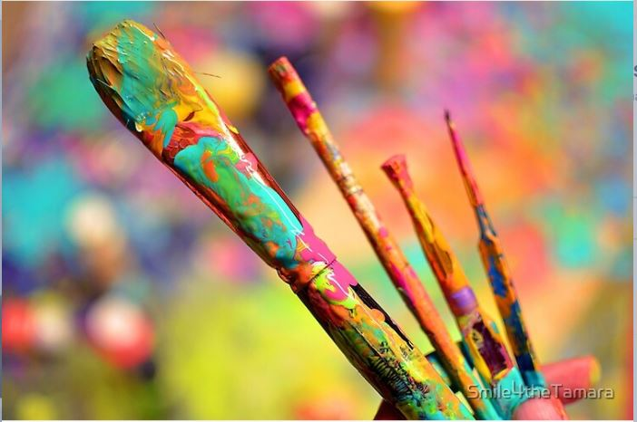 bright paint covering multiple paint brushes with a blurry background