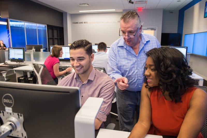 Two students review their project in the Newhouse media lab.