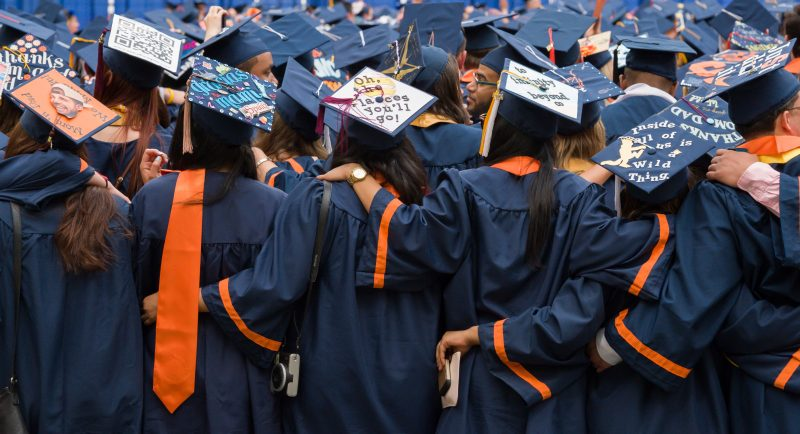 Graduating students embracing.