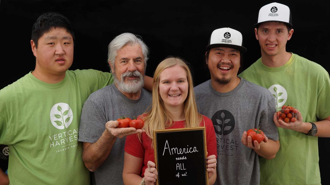 five people holding tomatoes looking into camera. the center person is holding a sign that says america needs all of us
