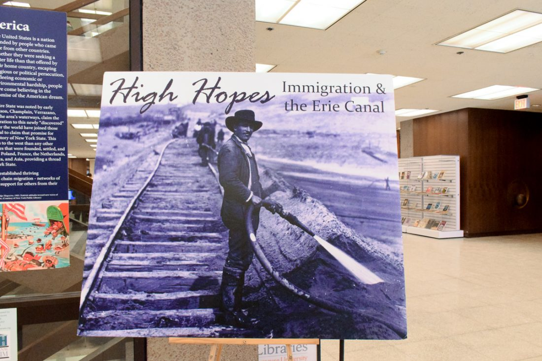 poster of b&w photo of immigrant standing near railroad with