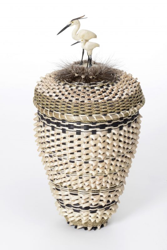 Tall woven basket in light tan and brown colors, top of lid has feather like weavings and a carved bird (egret) made of stone
