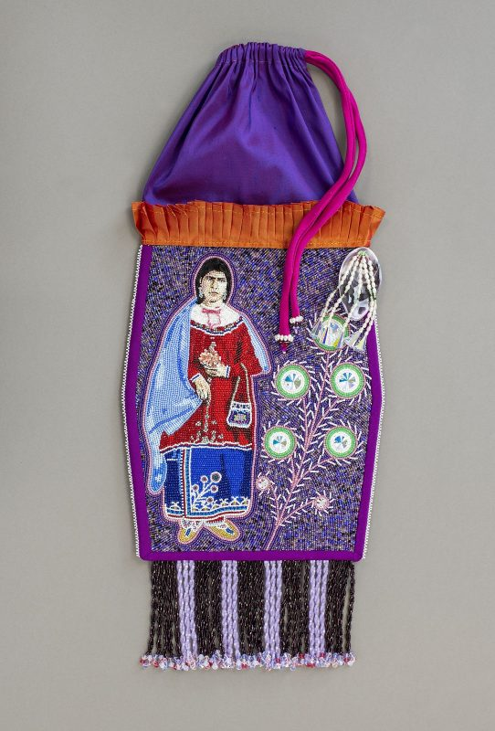 Purple oblong drawstring pouch with tassels at bottom and beadwork in middle depicting a person on the left and plant on the right