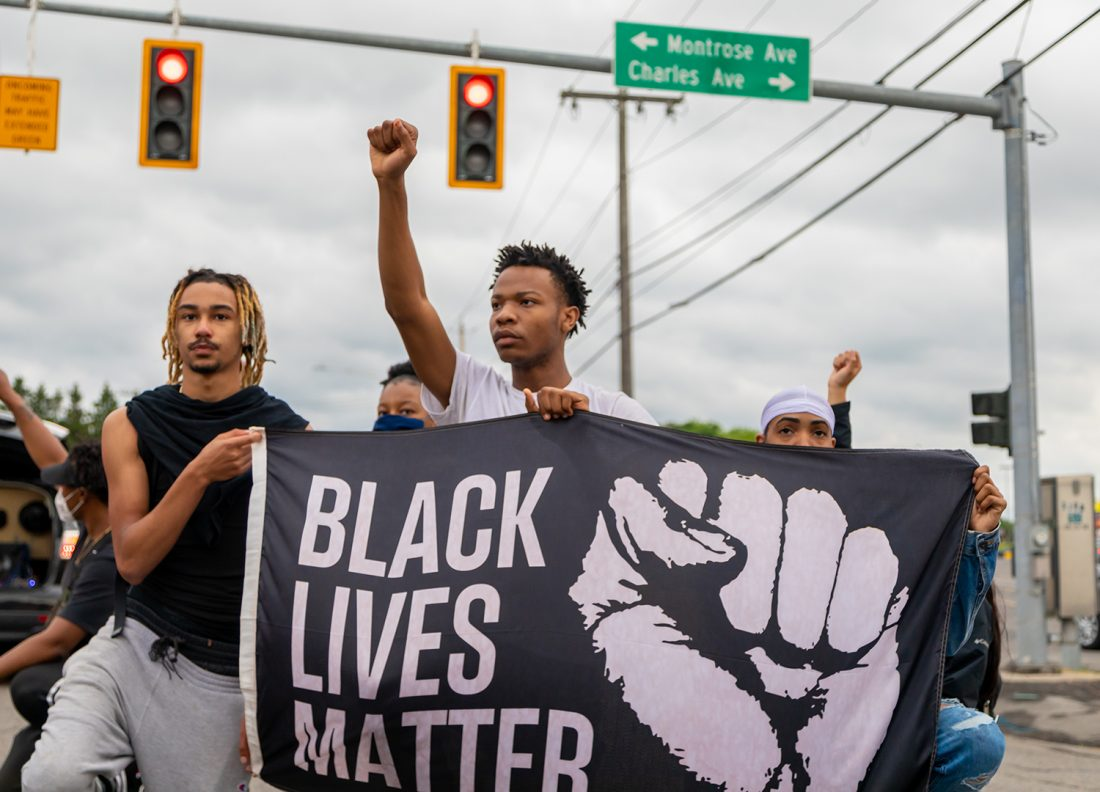 Three young Black men hold Black Lives Matter flag