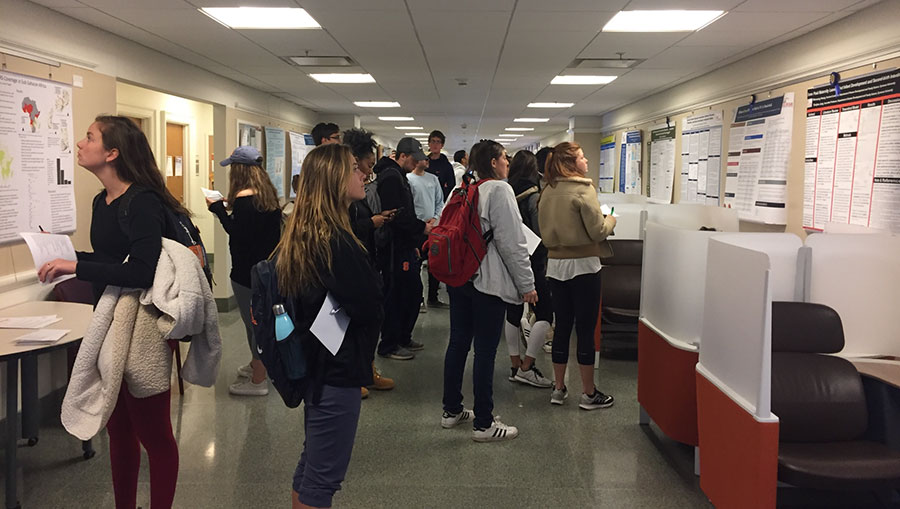 A large group of persons are looking at posters hanging in a hallway