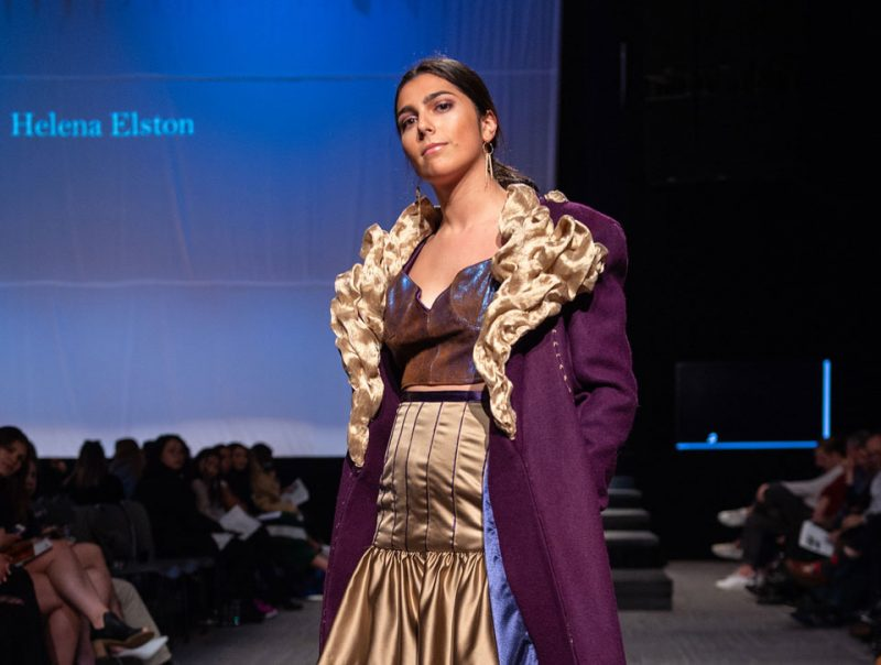 A model poses on stage in a student design during a fashion show.