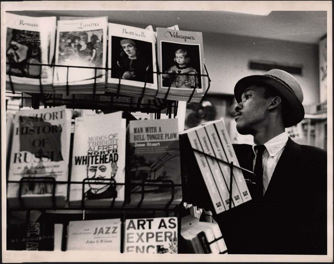Black and white photo of a man in a bookstore