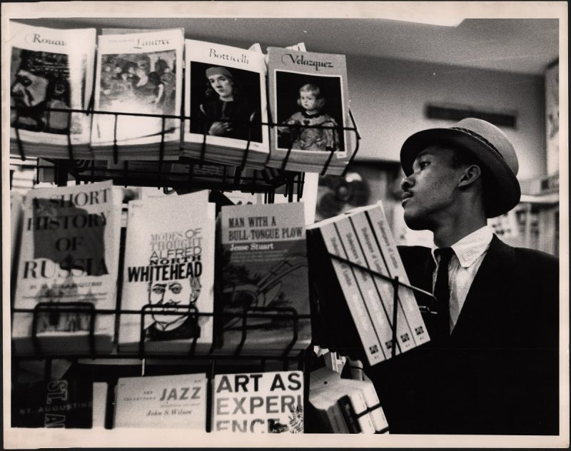 Black and white photo of man in bookstore