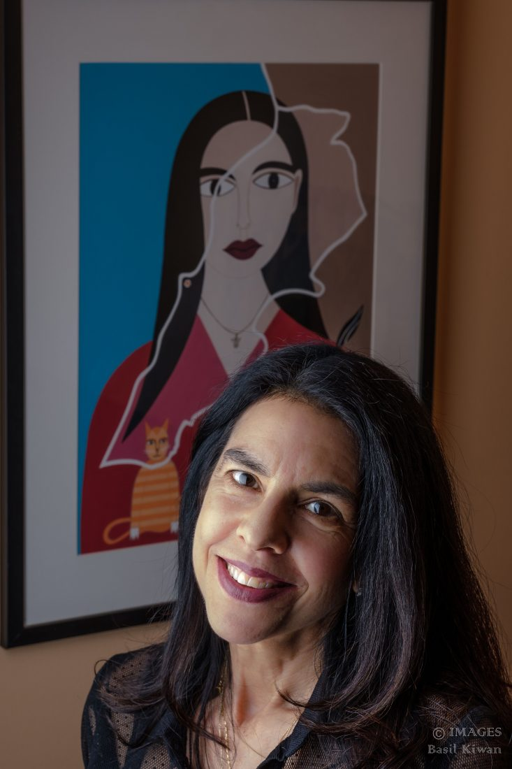 portrait of woman with long hair in front of artwork
