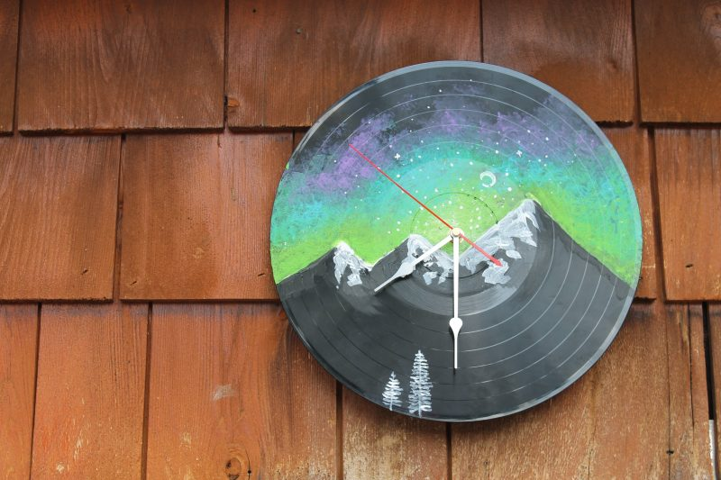A vinyl record clock with a mountain painted on it.