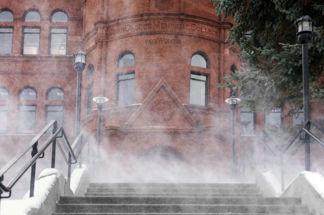 Wind blowing snow across the entrance of Crouse College