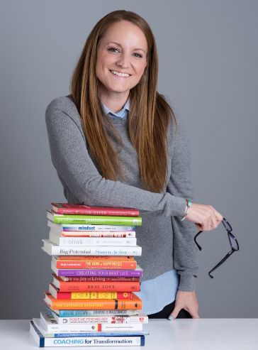 Jaime Weisberg Standing with a stack of books