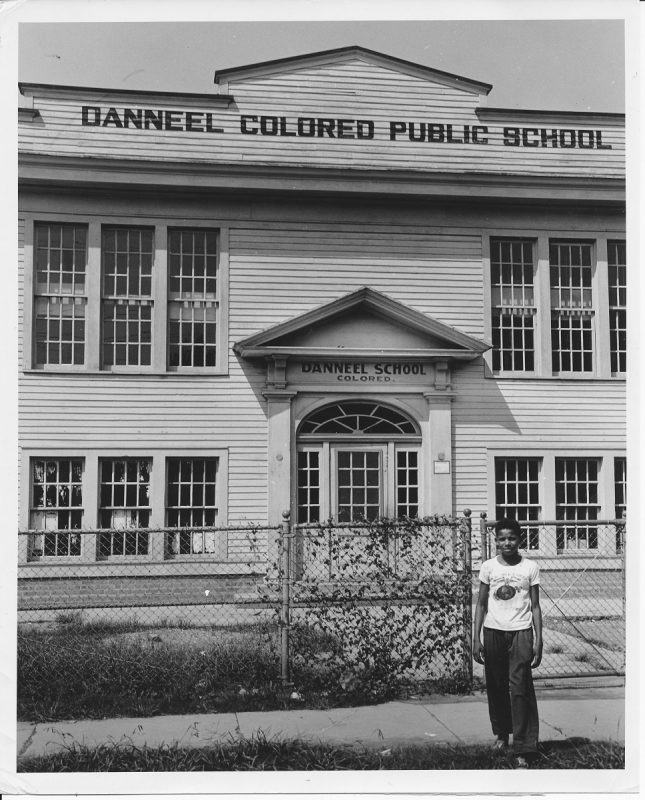 Photo of a Young boy in front of a school