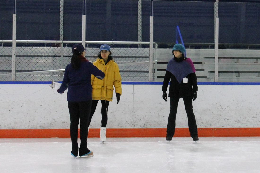 A skating instructor teaches ice skating to two students.
