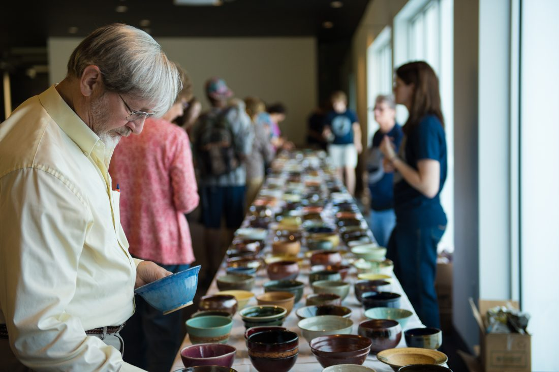 Community members survey ceramic bowls to take home during the Empty Bowls event.
