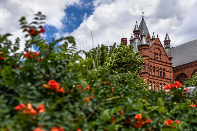 Crouse College rises above green foliage with orange flowers.