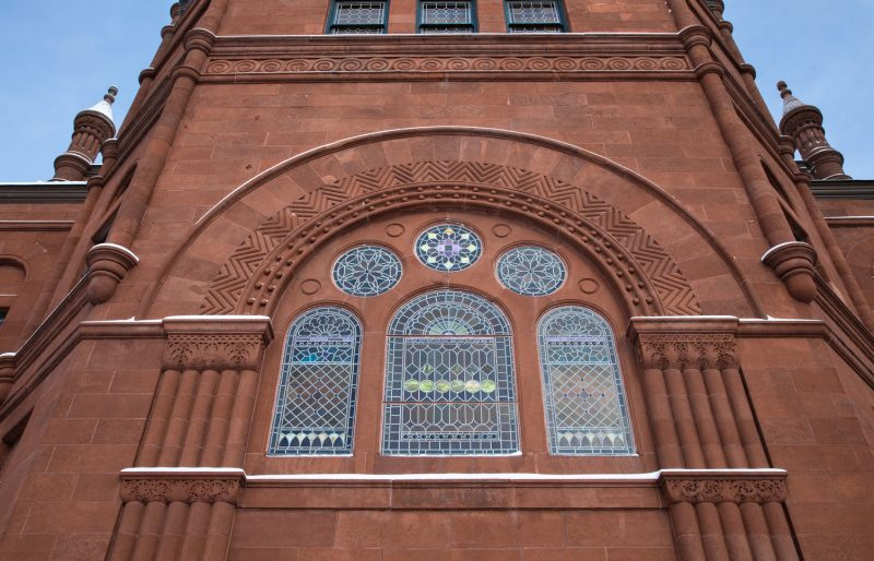 Snow sits on the edges of Crouse College's exterior architecture surrounding a large stained glass window.