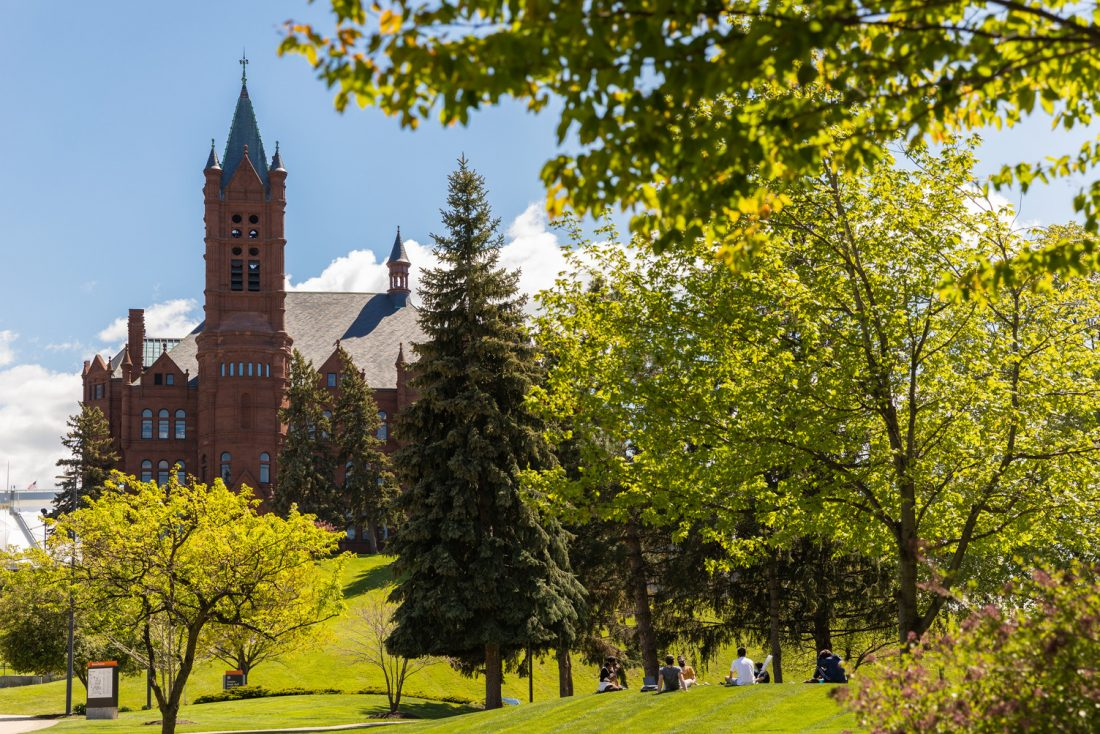 A class meets outside on a spring day with Crouse College in the background.