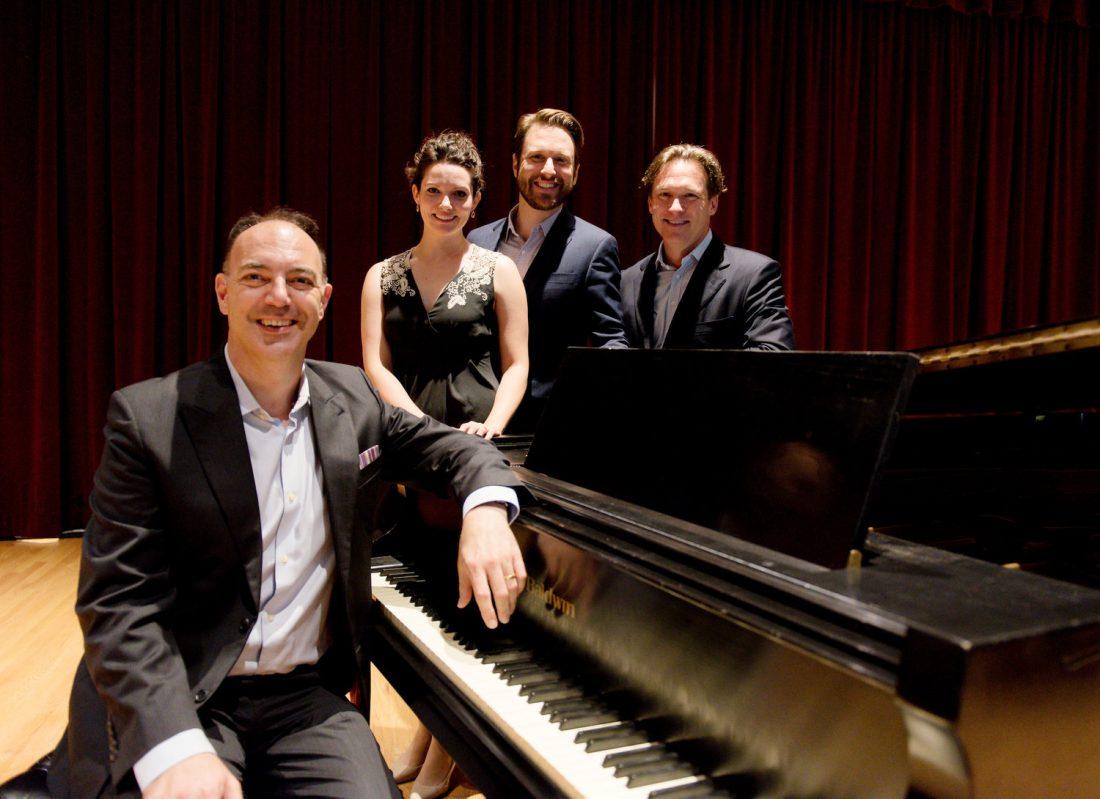 Group standing around piano