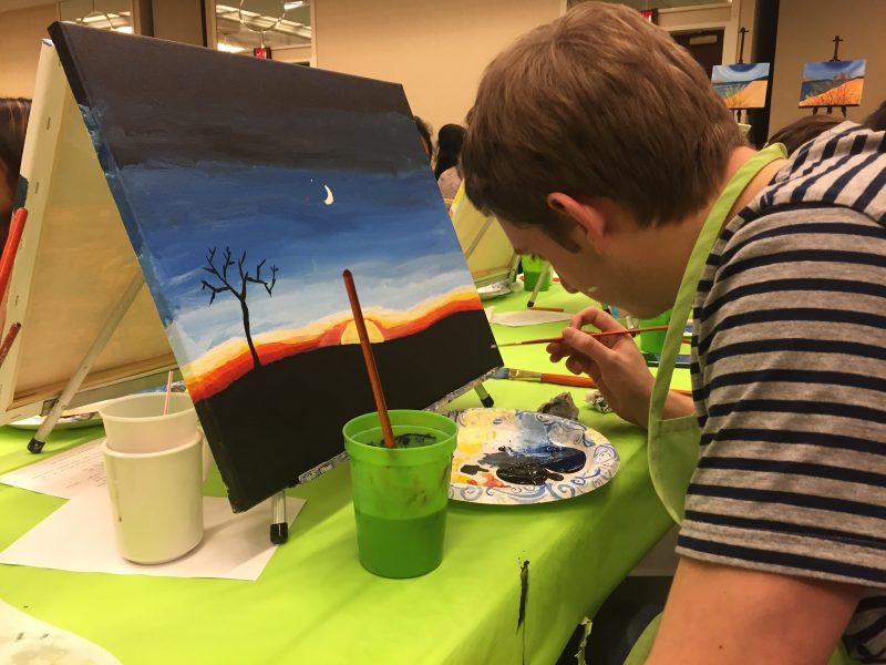 A student paints a desert sunset at Orange After Dark Paint Night