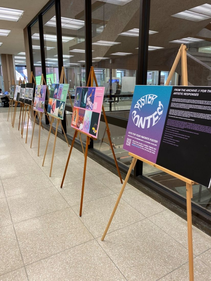 posters set up on easels near glass stairwell of Bird Library