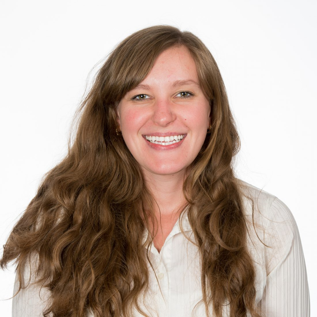 A close-up color photo of Dr. Alesia Prakapenka, smiling with full-teeth and long, wavy brown hair against a solid background.
