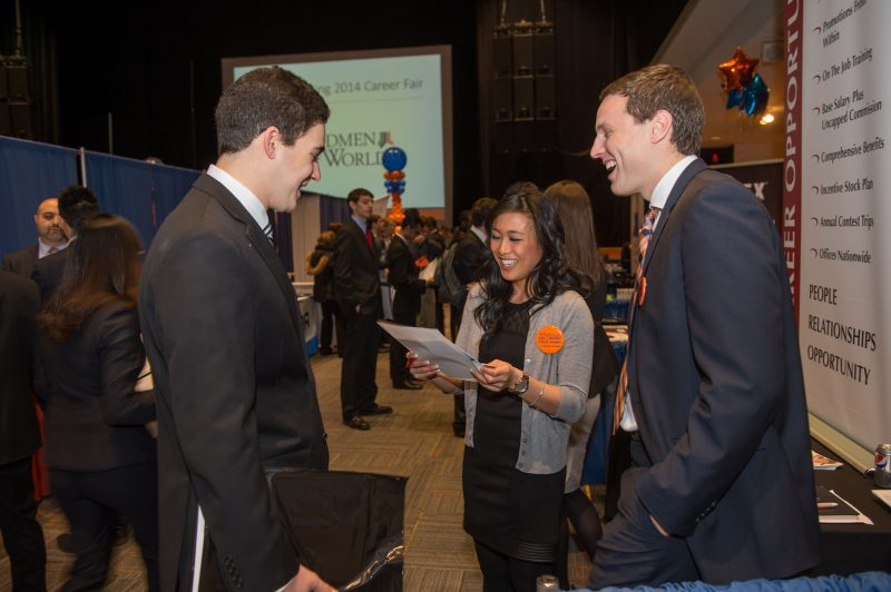 Well-dressed students laugh with a recruiter at the spring career fair.