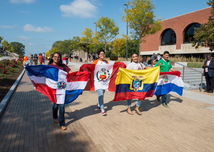 A group of Latinx students walk down Einhorn Family Walk with various flags of their countries.