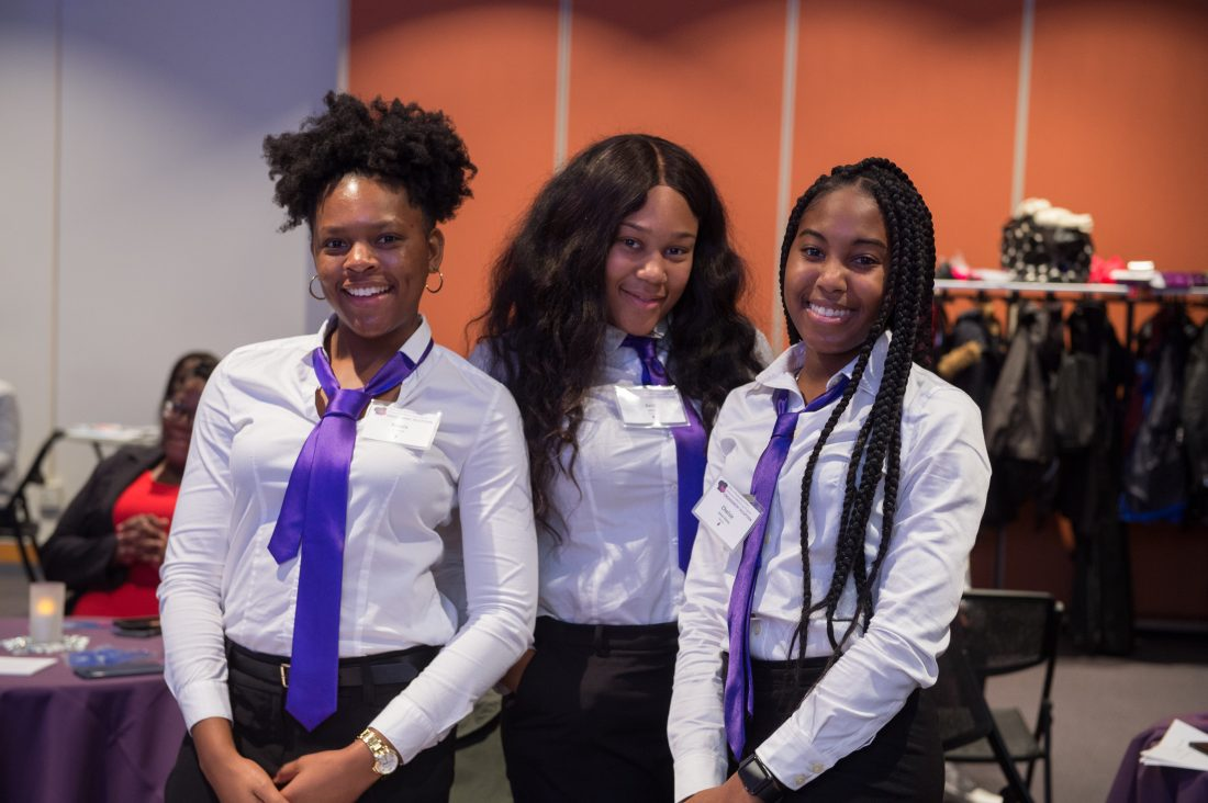 A group of smiling Dimensions mentors and mentees gather on campus in white button-up shirts with purple ties.