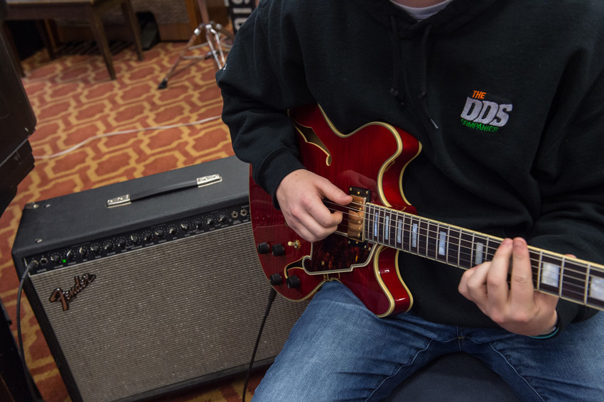 A student practices the guitar .