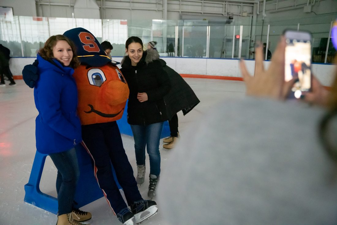 A student takes a photo of their friends on the ice rink posing with Otto the Orange during Late Night at the Rink.