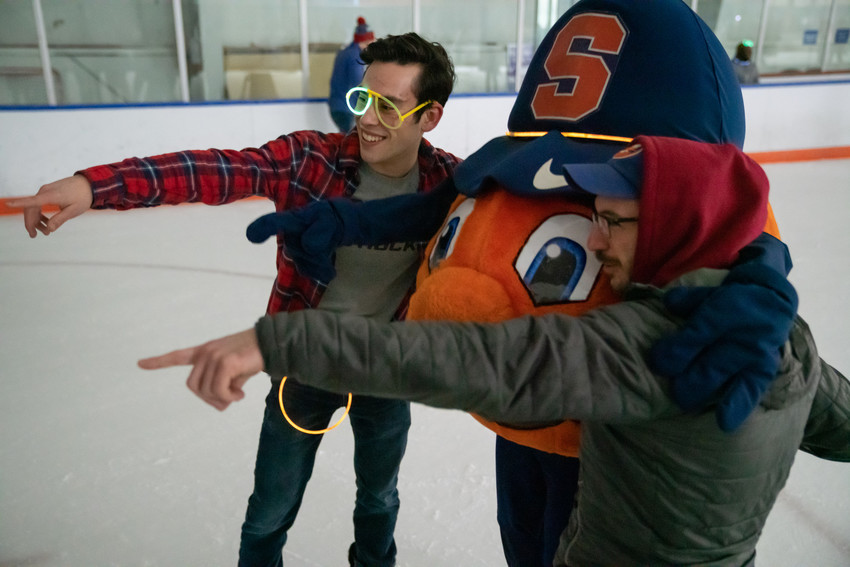 Students point at the camera with Otto the Orange at glow skate