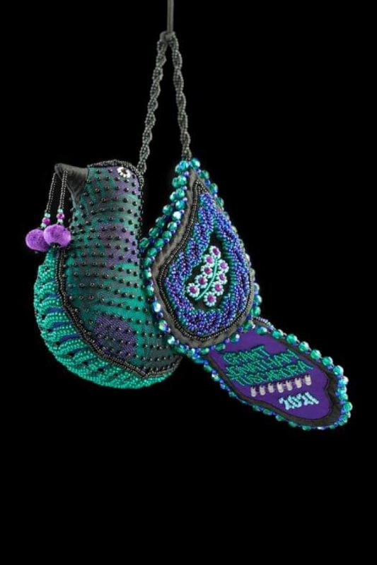 Woven and beaded bird with dark teal and purple coloring , a beaded cherry handing from his mouth, and sparkling beads across its surface