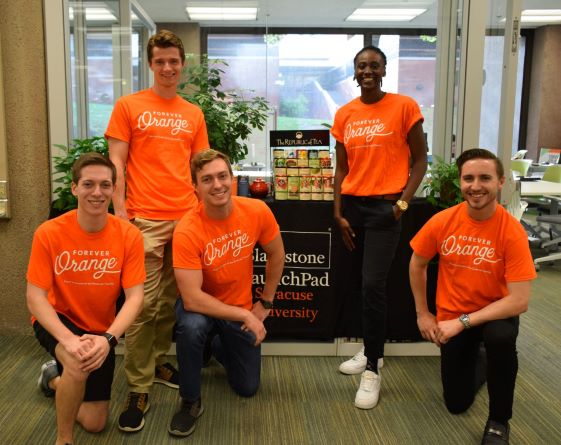 5 students wearing forever orange t-shirts standing in front of LaunchPad with Republic of Tea display behind them