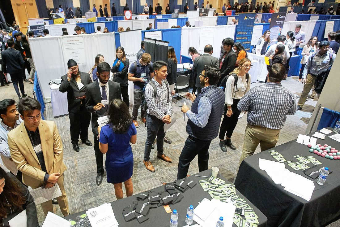 Student shaking hands and speaking with employers at the iSchool career fair.