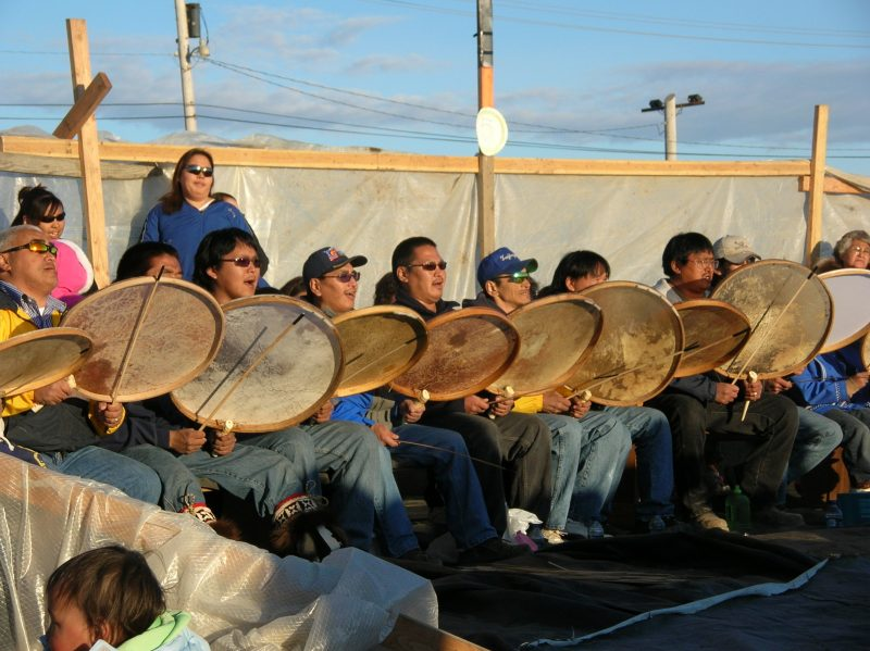 Indigenous people sitting in a line playing traditional drums