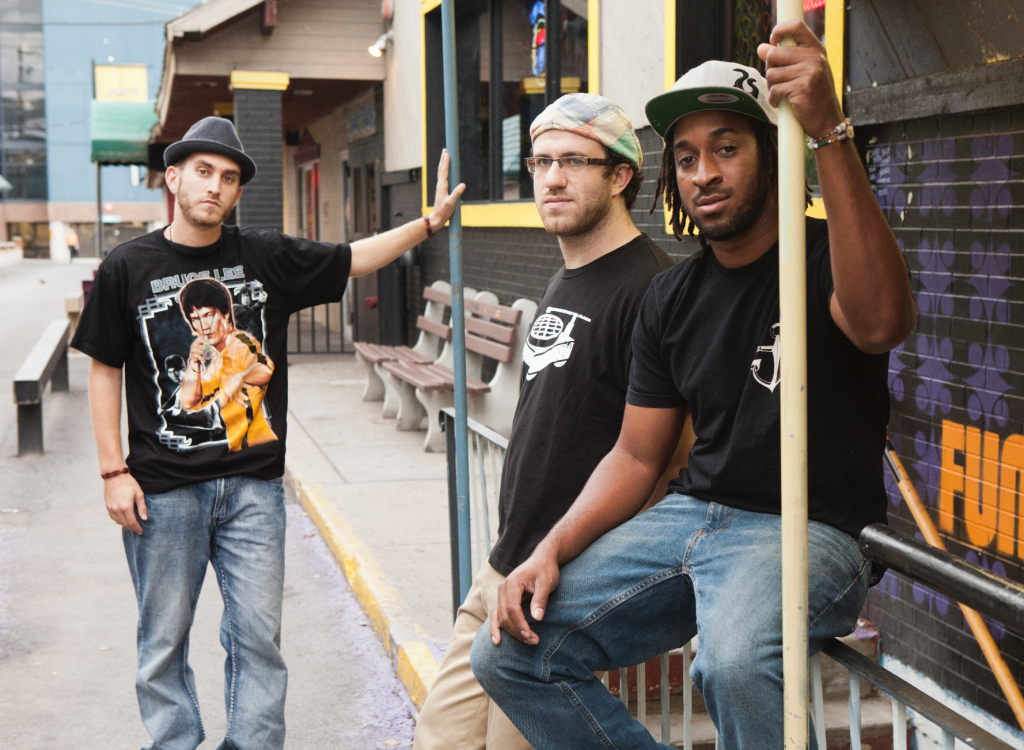 Three members of band sophistafunk pose together in an alleyway