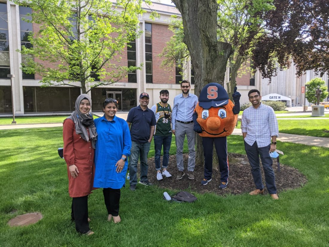 Otto standing with students under a tree between Hendricks Chapel and Physics Building.